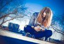 Od ilu lat można mieć Instagram? Młoda blond kobieta siedząca na ziemi ubrana w niebieską jeansową kurtkę, grantowe jeansy i kolorowe trampki